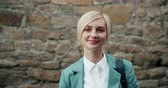 individualidade : Portrait of beautiful blonde student smiling looking at camera standing near brick wall outdoors alone. Happy millennials and urban lifestyle concept.