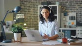 развлекать : Attractive young lady in headphones is listening to music at work and working with laptop alone enjoying gadget and entertainment. People, devices and fun concept.