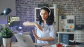 accogliente : Playful girl brunette is dancing enjoying music in headphones and using laptop in cozy illuminated office in the evening. People, gadgets and job concept.