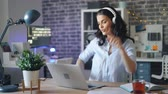 развлекать : Cute young woman is having fun in illuminated office listening to music in headphones dancing using laptop sitting at table alone. People, youth and job concept.