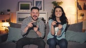 manette de jeu : Man and woman beautiful couple are playing video game in apartment, happy girl is winning celebrating success laughing. People, devices and fun concept.