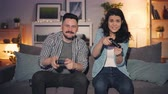 развлекать : Cute couple husband and wife are playing video games at home using joysticks moving hands looking at screen, joyful man is winning. Fun and youth concept.