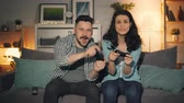 развлекать : Joyful young people man and woman are playing video games at home having fun together late at night sitting on couch. Millennials and modern technology concept.