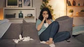 lagrima : Upset woman is drinking alcohol crying watching sad movie on TV at home sitting on sofa alone. Unhappy young people, negative emotions and television concept. Archivo de Video