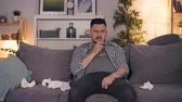 deprimovaný : Sad guy is drinking alcohol crying and wiping face with paper tissue sitting on sofa watching TV late at night. People, depression and apartment concept. Dostupné videozáznamy