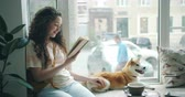čtenář : Pretty young lady is reading interesting novel in cafe on window sill and stroking cute pet dog shiba inu breed. Happy youth and domestic animals concept.