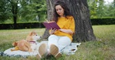 čtenář : Slow motion of attractive young woman reading book in park on summer day sitting on lawn with shiba inu dog. Hobby, lifestyle and youth culture concept. Dostupné videozáznamy