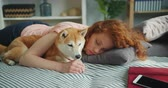 štěně : Beautiful young lady is sleeping on couch at home hugging adorable puppy lying together resting. Youth lifestyle, happy people and animals concept.