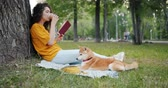 čtenář : Relaxed girl is drinking coffee and reading book in park sitting on lawn with shiba inu dog enjoying leisure time. Modern lifestyle, people and pets concept. Dostupné videozáznamy