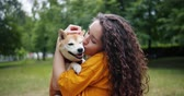 acariciando : Portrait of kind young lady holding adorable shiba inu dog kissing and hugging pet standing in park in summer. Feelings, friendship and love concept. Vídeos