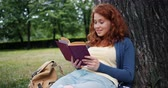 čtenář : Cheerful redhead girl reading book outdoors in park smiling relaxing sitting on grass alone enjoying story and nature. People, lifestyle and summer concept. Dostupné videozáznamy