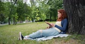 storie : Beautiful young woman is reading book sitting on blanket under tree in park and smiling enjoying summertime and literature. People and lifestyle concept.