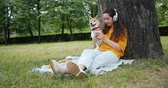 芝 : Beautiful young woman is using smartphone and listening to music in wireless headphones in green summer park with dog. Leisure time and animals concept.