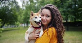 芝 : Portrait of pretty girl loving dog owner standing in park with her beautiful pet, smiling and looking at camera. Adorable animals and summer nature concept. 動画素材