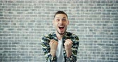 fäuste : Portrait of lucky guy handsome bearded man raising fists celebrating success and luck expressing positive emotions standing against brick wall background. Stock Footage