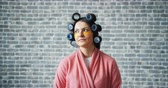 curlers : Portrait of pretty young lady housewife with hair rollers and eye patches standing alone on brick wall background. Beauty, youth and lifestyle concept.