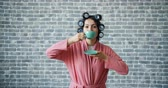 curlers : Portrait of young lady with hair curlers wearing bathrobe holding cup drinking tea then smiling on brick background. People, drinks and lifestyle concept.