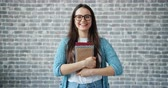 čtenář : Portrait of pretty girl in glasses diligent student holding books and smiling standing on brick wall background. People, education and lifestyle concept. Dostupné videozáznamy