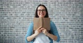 čtenář : Portrait of happy girl in glasses reading book hiding face then smiling standing on brick wall background. Youth culture, education and lifestyle concept.