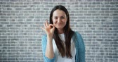 approve : Portrait of cheerful woman showing OK hand gesture smiling looking at camera standing against brick wall background. Millennials and evaluation concept. Stock Footage