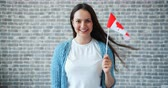mávání : Portrait of beautiful girl holding Canadian flag on brick wall background smiling looking at camera alone. Travelling, world countries and people concept. Dostupné videozáznamy
