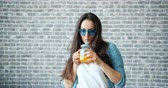 かんきつ類の果実 : Pretty lady in sunglasses is drinking orange juice and smiling standing on brick wall background wearing casual clothes. People, drinks and healthy lifestyle concept. 動画素材