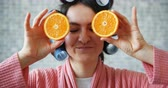 curlers : Portrait of joyful girl with hair rollers holding fresh oranges hiding eyes showing tongue having fun on brick wall background. People and fruit concept. Stock Footage