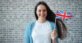 mávání : Portrait of pretty young woman with British flag standing alone on brick wall background smiling looking at camera with happy face. Tourism and world concept.