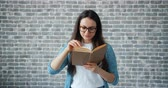 образованный : Serious girl in glasses is reading interesting book turning page standing alone on brick wall background. Modern lifestyle, education and youth concept.