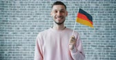 mávání : Portrait of happy guy holding German flag and smiling standing on brick wall background alone wearing casual clothing. Patriots, travelling and countries concept.