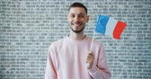 mávání : Portrait of happy young man with French national flag on brick wall background standing looking at camera and smiling. People, tourism and nationality concept. Dostupné videozáznamy