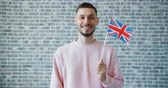 вентилятор : Portrait of handsome man with British flag on brick wall background standing smiling and looking at camera. Happy people, tourism and countries concept.