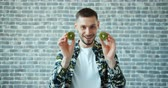 киви : Portrait of handsome young man with kiwi fruit on eyes smiling standing on brick wall background having fun. Healthy food, modern lifestyle anf youth concept.