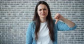schaam : Portrait of unhappy girl with long black hair showing thumbs-down on brick wall background. Dislike gesture, disappointed people and attitude concept. Stockvideo
