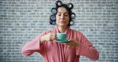 curlers : Young woman with curlers on hair holding cup drinking coffee looking around standing alone on brick wall background. People, drinks and emotions concept. Stock Footage