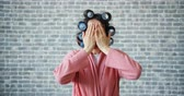 curlers : Portrait of funny girl with hair curlers playing hide and seek hiding eyes with hands then shouting standing alone on brick wall background. People and fun concept. Stock Footage