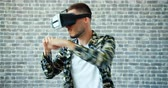 развлекать : Portrait of man in vr glasses boxing moving hands on brick wall background enjoying digital sports. Modern gadgets, young people and entertainment concept.