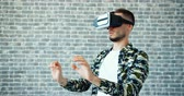 развлекать : Portrait of guy with augmented reality glasses moving hands on brick wall background enjoying syberspace experience. People, entertainment and gadgets concept. Стоковые видеозаписи