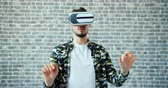 развлекать : Portrait of man using virtual reality glasses moving hands standing on brick wall background enjoying cool gadget. People, devices and entertainment concept. Стоковые видеозаписи