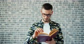 čtenář : Portrait of bearded guy in glasses diligent student reading book standing alone on brick wall background. Literature, education and modern lifestyle concept.