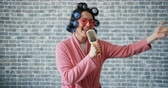 curlers : Woman with hair curlers, glasses and bathrobe is singing in hairbrush having fun moving arms standing on brick wall background. People, joy and music concept.