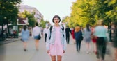 stillness : Zoom in time lapse of pretty teenager standing in street with backpack looking at camera with serious face. Modern lifestyle, people and metropolis concept. Stock Footage