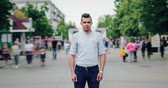 stillness : Time lapse of good-looking young Arab with serious face standing alone in street looking at camera when crowd of people is rushing around. Youth and life concept.
