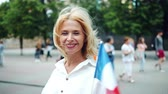 вентилятор : Slow motion portrait of pretty French lady holding flag of France outdoors smiling looking at camera. Patriotism, nationality and world travelling concept.