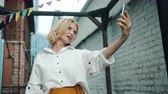 kifinomult : Slow motion of pretty middle aged woman taking selfie with smartphone outdoors posing for mobile camera having fun. People, devices and photo concept. Stock mozgókép