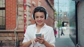 청소년 문화 : Portrait of cheerful young lady enjoying music in headphone using smartphone outdoors walking having fun. People, modern devices and city lifestyle concept. 무비클립