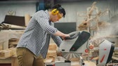 montáž : Man is sawing wood in workshop using electric saw working alone wearing goggles and safety headphones. People, industry and small business concept. Dostupné videozáznamy