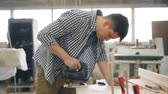 зажимное приспособление : Young carpenter is using jigsaw power instrument to saw wood in workshop manufacturing handmade wooden furniture. People, business and woodwork concept.