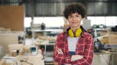 пересек : Portrait of beautiful young woman carpenter standing in workroom with crossed arms looking at camera and smiling. Small business and hard-working youth concept.