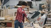 montáž : Beautiful young girl sawing timber with circular saw in wood workshop working alone cutting wooden plank then looking at woodware. People and job concept.